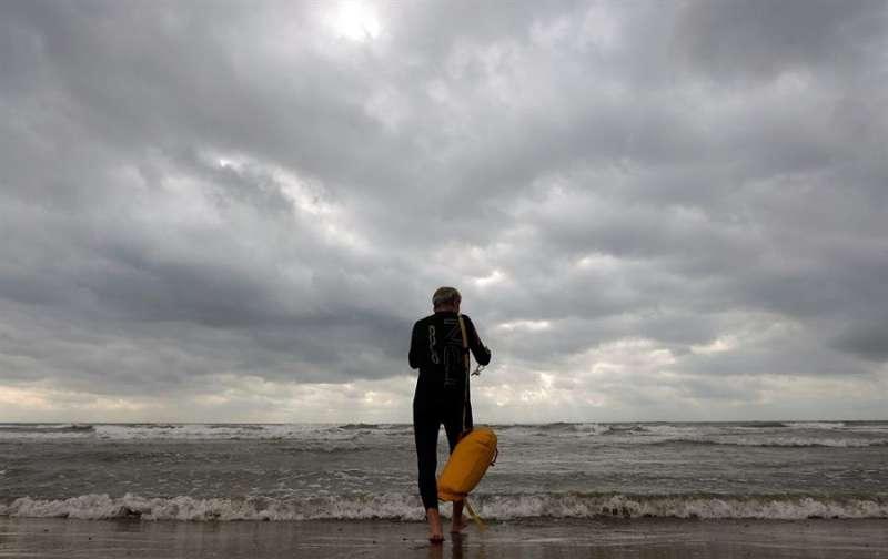 Un nadador en la playa de València, en un día nublado, en una imagen de esta semana. EFE/Kai Försterling