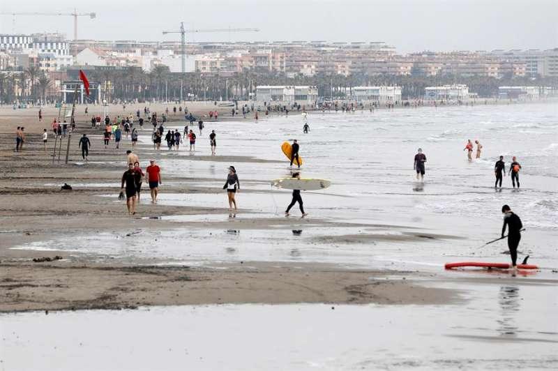 Cientos de personas pasean, durante la franja horaria permitida, en la playa de la Malvarrosa. EFE