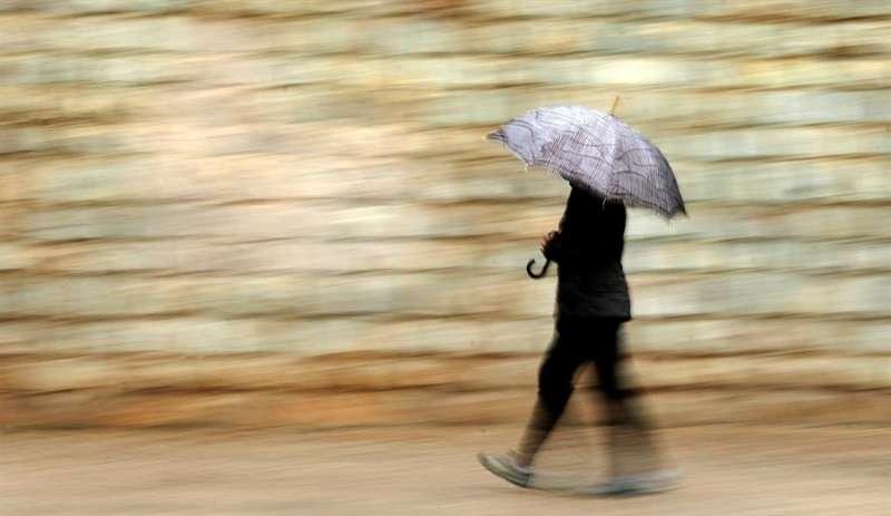 Una persona se protege de la lluvia con paraguas este jueves en València. EFE
