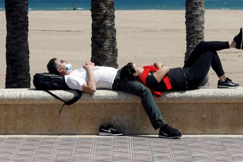 Dos personas aprovechan la tregua de la lluvia para descansar al sol de la playa de la Malva-rosa, una imagen de los últimos días de abril. EFE/Biel Aliño/Archivo