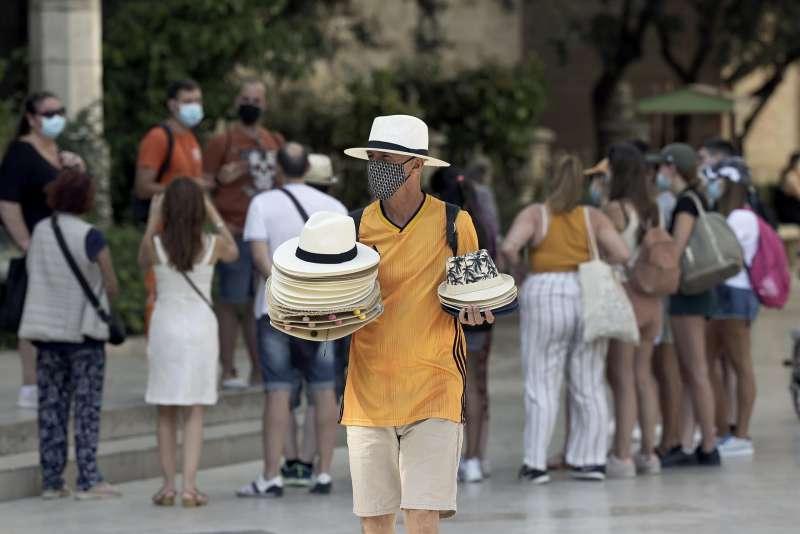 En la imagen, un vendedor de sombreros frente al sol y el calor.