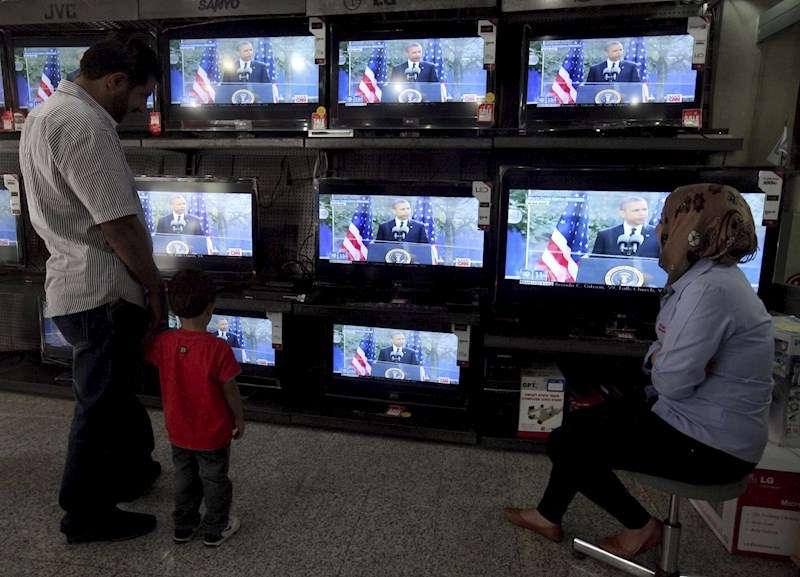 Un padre y un hijo observan varios televisores en una imagen de archivo. EFE
