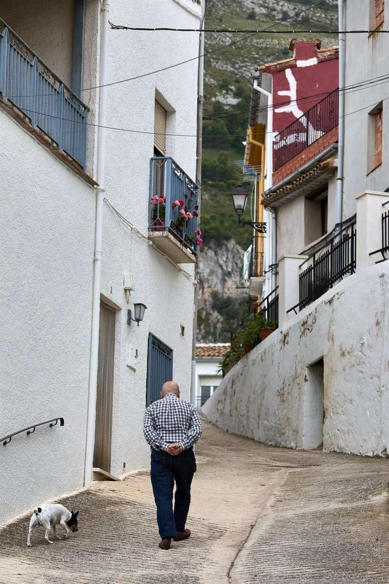 En la imagen un vecino del pueblo valenciano de Famorca pasea junto a su perro. EFE/Natxo Francés