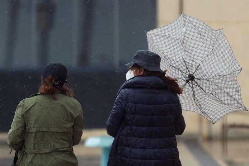 Dos personas tratan de protegerse de la lluvia con un paraguas.