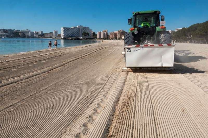 Un tractor limpia una playa para ponerla a punto de cara a su posible utilización por los bañistas. EFE