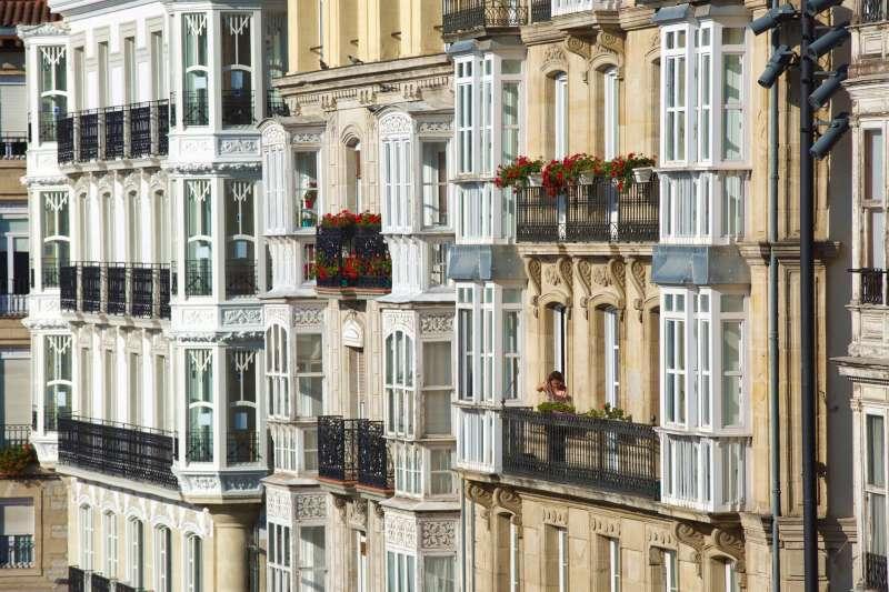 Una mujer riega sus plantas en un balcón.