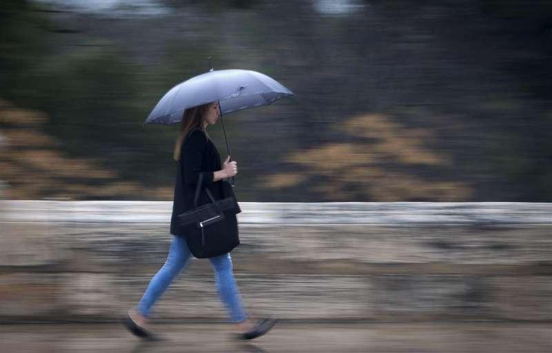 Una joven se protege de la lluvia con un paraguas.