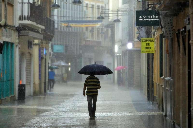Un hombre camina bajo una intensa lluvia en una imagen de archivo tomada en pleno centro de Gandia.