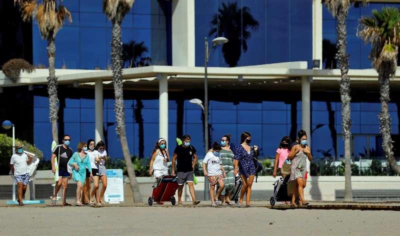 Varias personas, todas ellas con mascarilla, se encaminan a la orilla de la playa de La Patacona de Alboraia