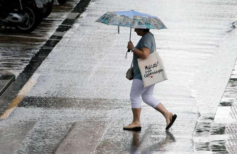 Una mujer camina bajo la lluvia con un paraguas.