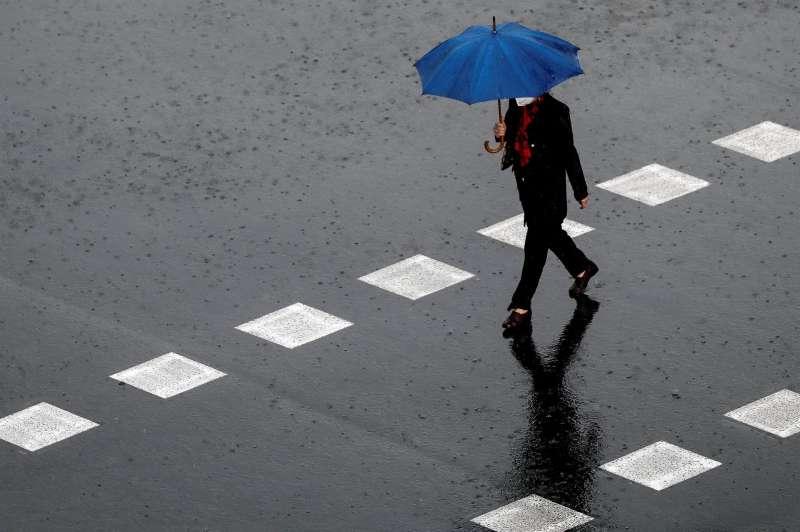 Una persona camina bajo una intensa lluvia.