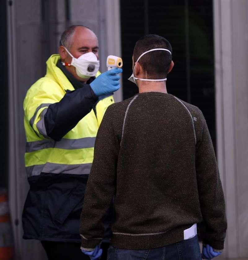 Imagen de archivo de un miembro de seguridad tomando la temperatura a un trabajador. EFE