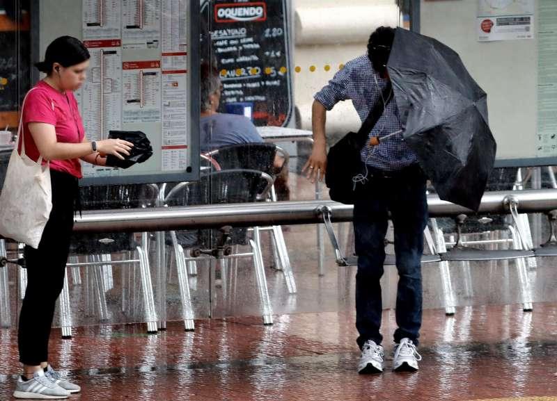 Dos personas se resguardan con el paraguas en plena tormenta. EFE