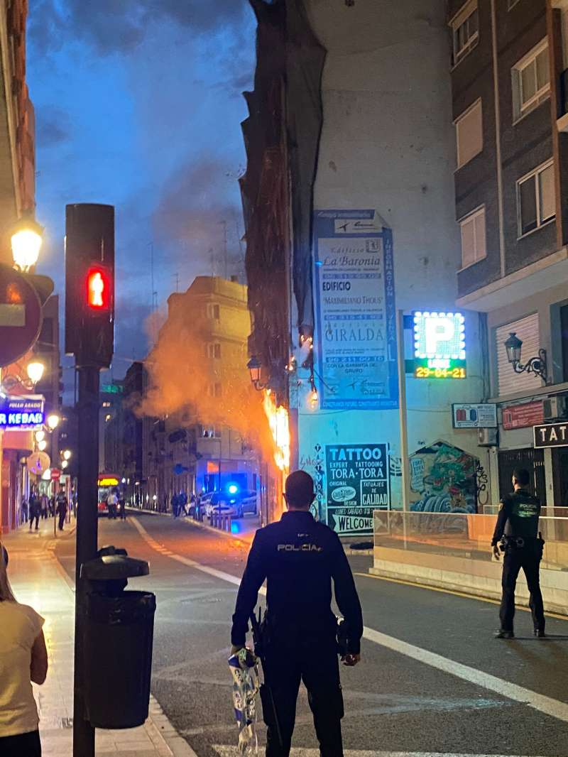 Un policía observa el fuego en su máximo apogeo. A. I.