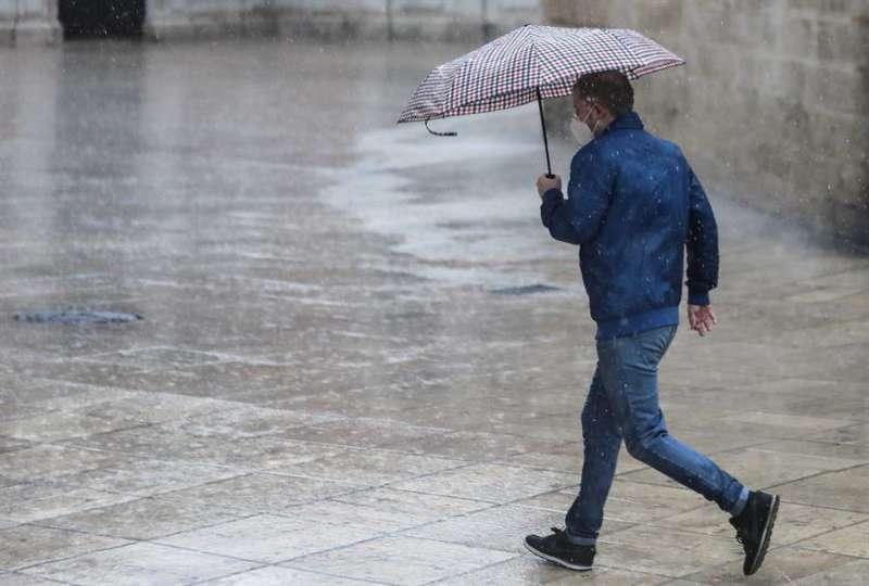 Una persona se protege de la lluvia con paraguas en el centro de Valencia.