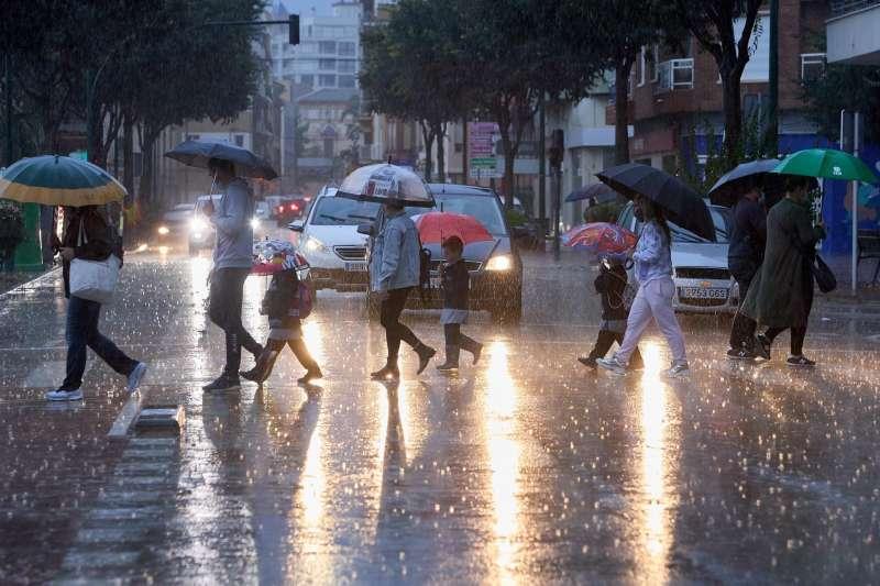 Varias personas cruzan una calle bajo la lluvia