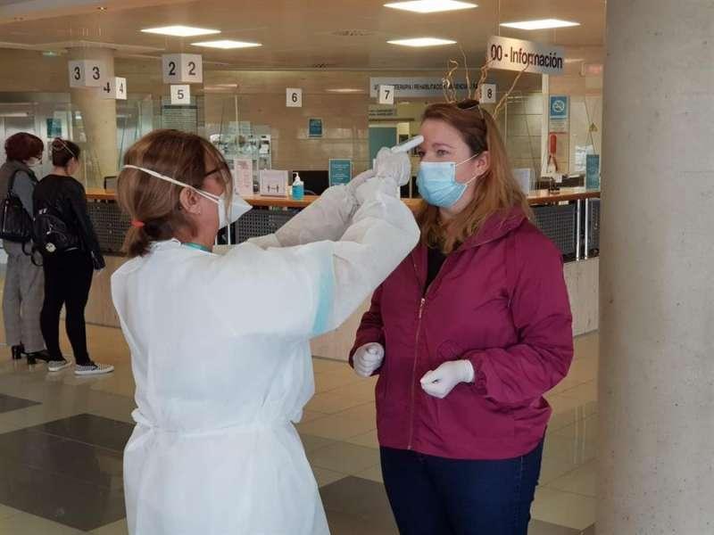 Una persona le toma la temperatura a una mujer en un centro de Quirónsalud, en una imagen facilitada por la compañía. EFE