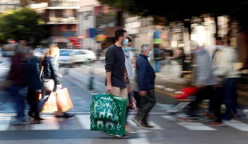 Imagen de archivo de varias personas de compras por el centro de València.
