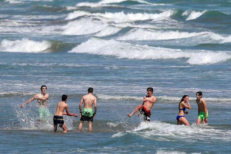 Un grupo de jóvenes disfruta de un baño en la playa.