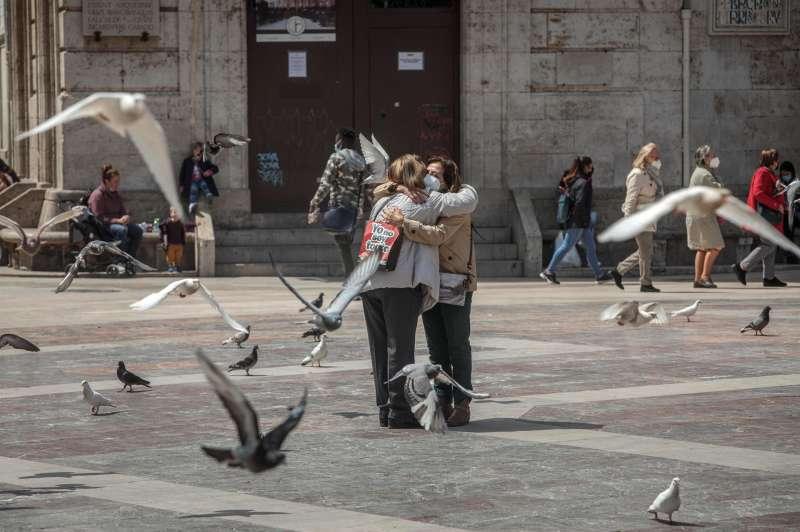 Dos personas se abrazan en una céntrica plaza de Valencia, un gesto dífícil de ver durante la pandemia.