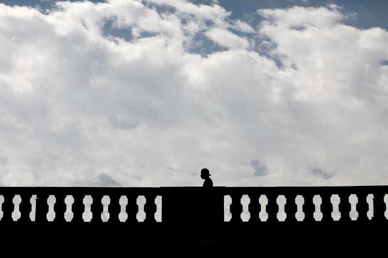 Una persona pasa por un puente de Valencia en un día nuboso.