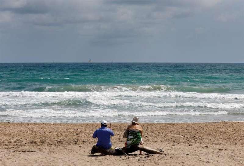 Una pareja disfruta del buen tiempo en la playa de El Saler. EFE
